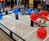 Robots maneuver colored balls in competition.
